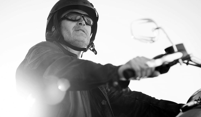 Closeup of Ken Schmidt on a Harley-Davidson motorcycle, wearing a helmet and sunglasses
